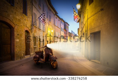 Beautiful street of tuscan San Quirico D'orcia town by night with old-fashioned scooter - stock photo