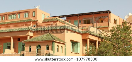 Beautiful streets of Marrakesh with its famous red houses and palms - stock photo