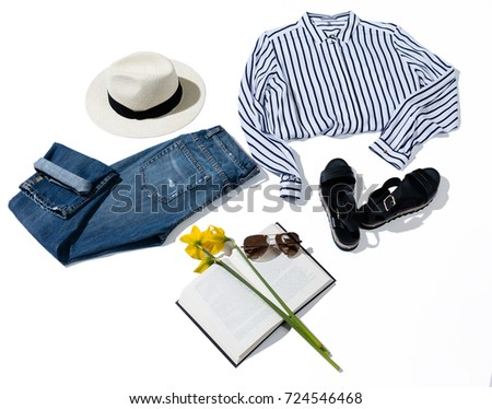 Beautiful striped shirt, jeans, hat, glasses, book, sandals and flowers on a white background, flat lay
