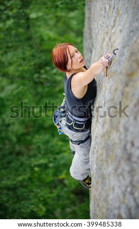 Beautiful strong female climbing steep stone wall in nature. Woman lead climber fastening carabiner at the next grip. Top view. - stock photo