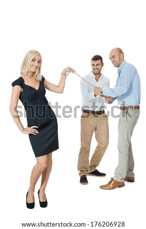 Beautiful strong fit woman demonstrating her dominance in a tug of war with two men pulling as hard as they can on the end of a rope she is holding while she remains nonchalant and glamorous, on white - stock photo