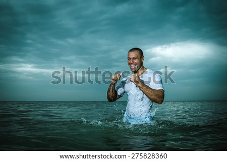 beautiful, strong, happy man in a wet t-shirt, the sea - stock photo