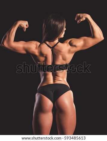 Beautiful strong woman in black underwear showing her muscles, on dark background