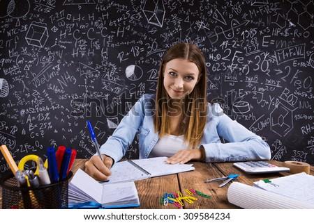 Beautiful student doing her homework in front of big blackboard - stock photo