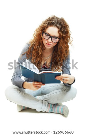 beautiful student girl holding book sitting on the floor bored - stock photo