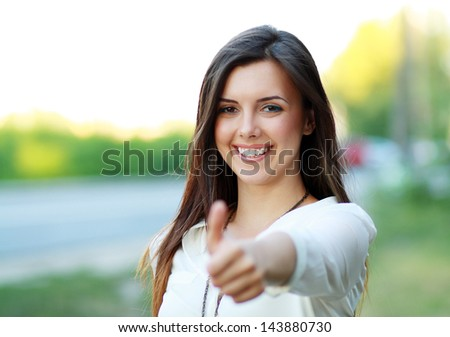 Beautiful student girl in white blouse lifts thumb upwards, against green of summer park. - stock photo