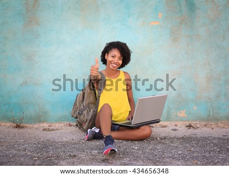 Beautiful student girl sitting on the floor using her laptop for study