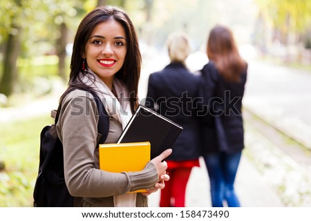 Beautiful student girl with books going to school. - stock photo