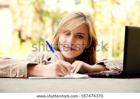 beautiful student girl with laptop in the park