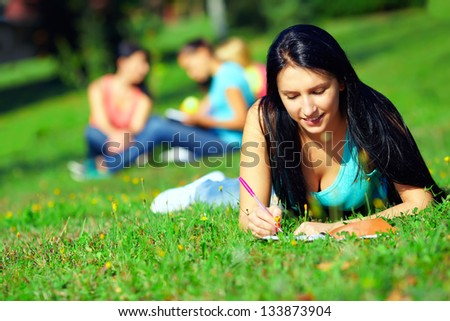 beautiful student on colorful sunny lawn - stock photo