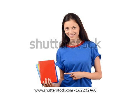 Beautiful student pointing to the blank red book cover. Attractive girl with blue t-shirt holding books. Isolated on white.