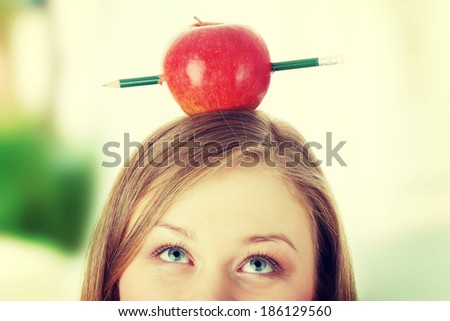 Beautiful student woman have one apple with pencil on her head - learning concept  - stock photo