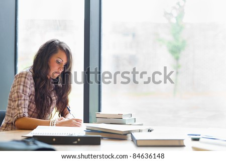 Beautiful student writing an essay in a library