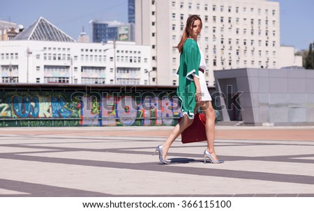 Beautiful style girl with long dark hair in summer white dress and green cape with red bag on heels walks in the city and enjoy a walk  - stock photo