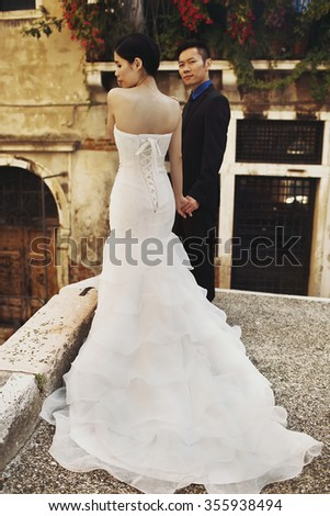 Beautiful stylish Asians bride and groom walking on the summer streets of Venice, Italy