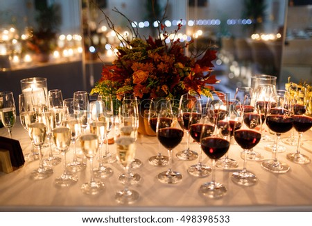 Beautiful stylish autumn bouquet and glasses of wine on the table