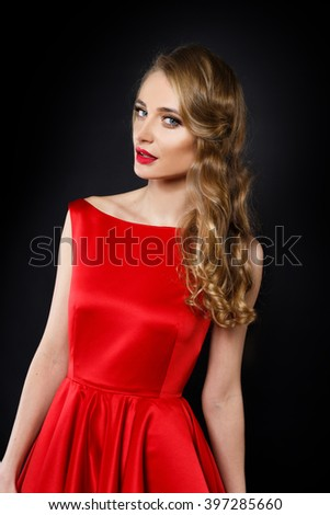 Beautiful stylish blonde woman in red dress on the black background