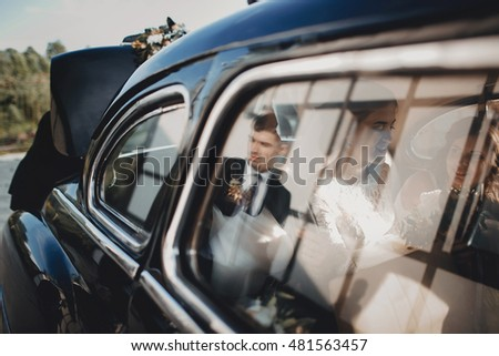 Beautiful stylish bride with bridesmaids in the retro car