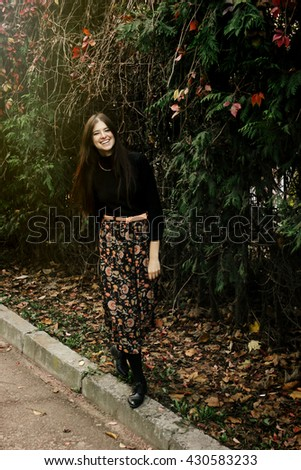 beautiful stylish brunette woman walking and smiling in autumn colorful park