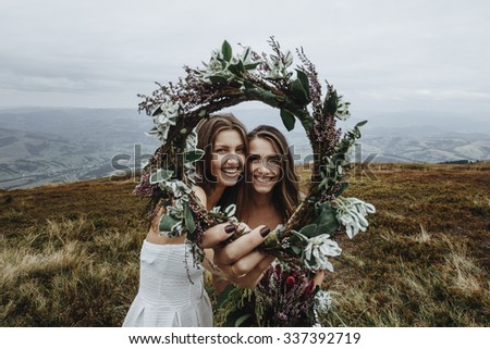 beautiful stylish fabulous happy bride and bridesmaid smiling on the background of the sunny stunning mountains