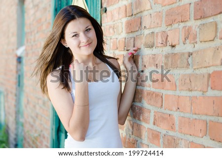 beautiful stylish fashion woman brunette girl having fun posing in urban city happy smiling & looking at camera on summer outdoor brick wall copy space background portrait image - stock photo