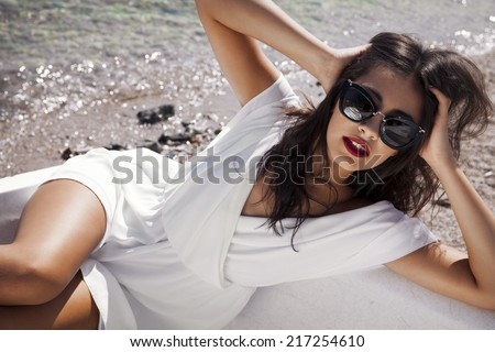 beautiful stylish female in white dress sitting in a boat.Horizontal summer shot. Toned in a warm colours..  - stock photo
