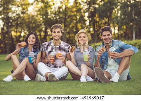 Beautiful stylish friends are drinking cocktails, eating sandwiches, looking at camera and smiling while resting in the park