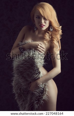 Beautiful, stylish, ginger girl with curly hair cover her nude body with fluffy fur. She has got amazing bracelet and earrings.