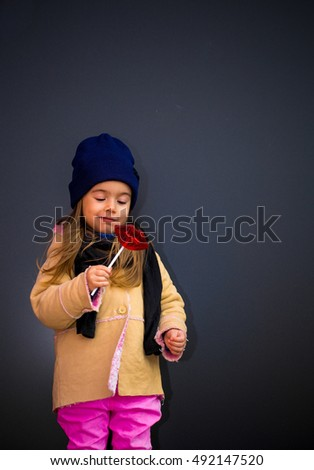 beautiful stylish girl in a black background of the walls, the joyous emotions of the girl, perky girl, big plump lips in the form of candy
