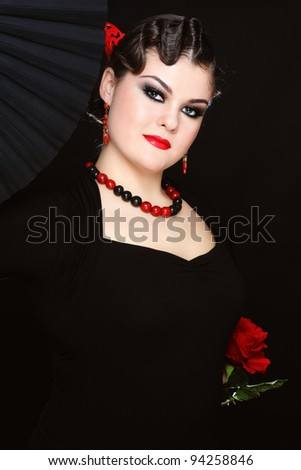 Beautiful stylish girl in flamenco costume with black fan and red rose
