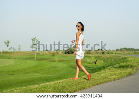Beautiful stylish girl is going to play golf - stock photo