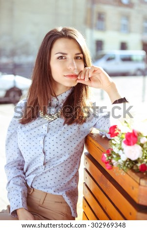 Beautiful stylish girl on the street. Business fashion, fashion trends, street look, business casual, street fashion. Portrait of a young woman in the street. Girl with flowers. - stock photo