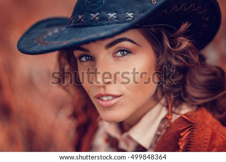 Beautiful stylish girl with a professional make-up wearing a cowboy hat, country style. closeup portraits