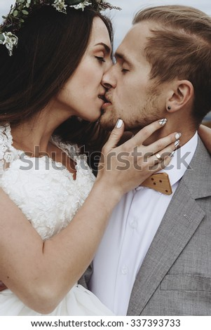 beautiful stylish groom holding fabulous happy emotional bride and kissing  on the background of the sunny stunning mountains