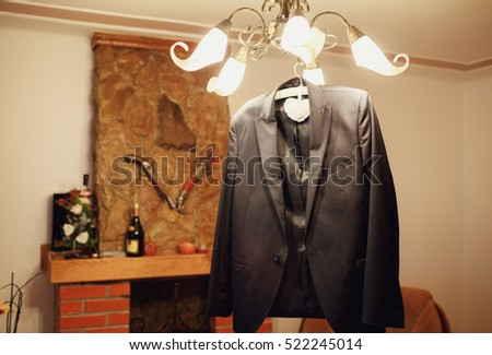 Beautiful stylish groom's suit hanging in the room