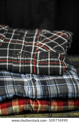 Beautiful stylish men's clothing, shirts folded in a pile on wooden background