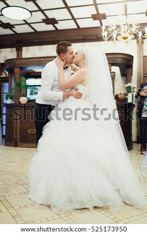 Beautiful stylish newlyweds kissing in the restaurant