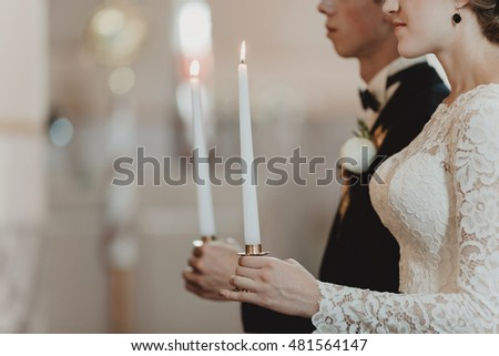 Beautiful stylish newlyweds on the wedding ceremony in the church