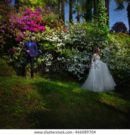 Beautiful stylish newlyweds posing in the garden