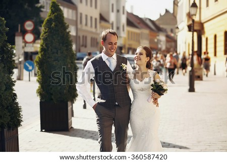 Beautiful stylish pair of newlyweds walking the streets of Budapest, Hungary, on a sunny bright day