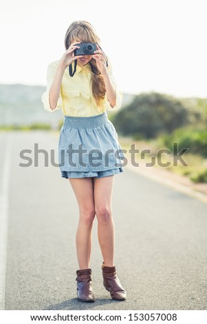 Beautiful stylish photographer taking a picture standing on a highway - stock photo
