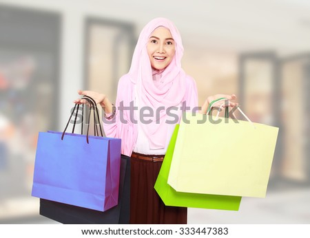 Beautiful stylish woman holding shopping bags in both hands at mall