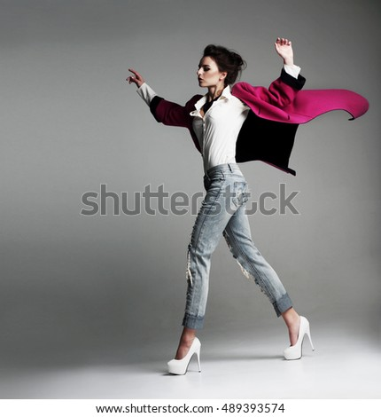 Beautiful stylish woman in a fashionable coat, walks in the studio. clothes flying. Fashion.