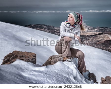 Beautiful stylish woman in snowy mountains, cute girl sitting on the hill of high mountain covered with snow, winter vacation concept
