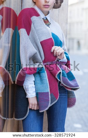 Beautiful stylish woman posing in city in modern glamorous outfit: colorful poncho, blue jeans. - stock photo
