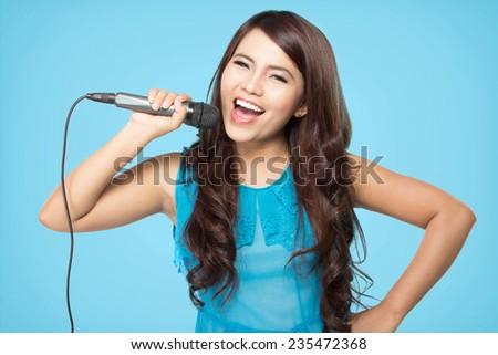 beautiful stylish woman singing karaoke isolated over blue background - stock photo