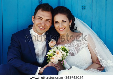 Beautiful stylish young bride and groom near the door of the church embracing and kissing - stock photo