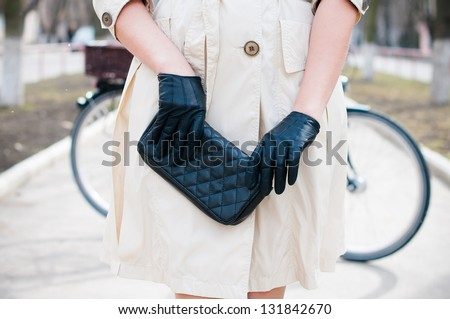 Beautiful stylish young European girl in a beige coat and a black hat and gloves with a city bicycle on a street - stock photo