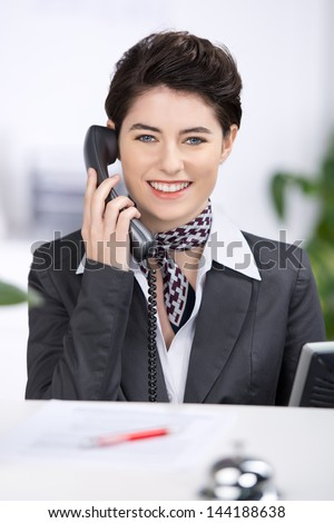 Beautiful stylish young female receptionist with a friendly smile talking on a telephone - stock photo