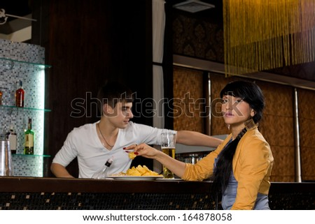Beautiful stylish young Hispanic woman with long braided hair sitting at a bar counter drinking a pint of beer and eating snacks as the barman works behind the counter - stock photo
